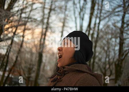 Vue de profil d'une femme asiatique en vêtements d'hiver dans une forêt à l'aube des premières neiges en hiver sunshine
