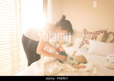 Cute little baby s'habiller par sa mère sur le lit dans la chambre à coucher