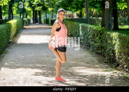 Les jeunes femmes d'Amérique latine attrayant avant d'entraînement fitness training session au parc avec un lac sain jeune femme se réchauffer à l'extérieur dans l'étirement il Banque D'Images