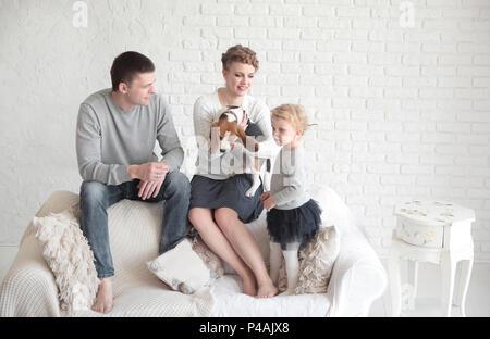 Portrait de parents heureux avec leur fille et l'animal de compagnie aimé d'une salle de séjour.photo avec place pour le texte Banque D'Images