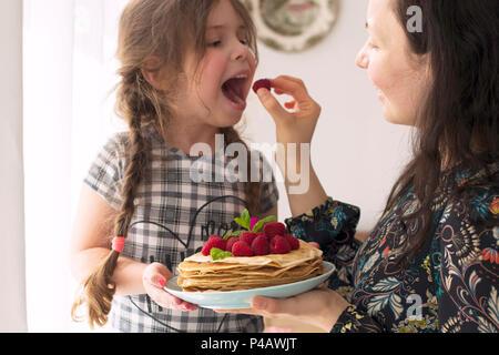 La maman et la fille sont titulaires d'une plaque avec des crêpes maison et de baies. Délicieux petit-déjeuner à la maison. Une famille heureuse. Bonjour, Banque D'Images