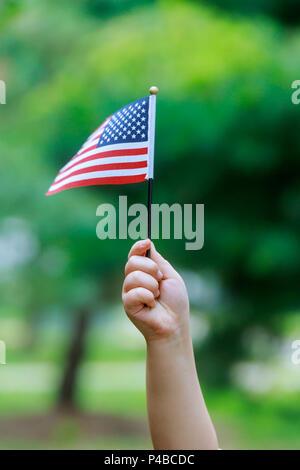 La jeune fille tient le drapeau américain dans ses mains. Close-up. Banque D'Images