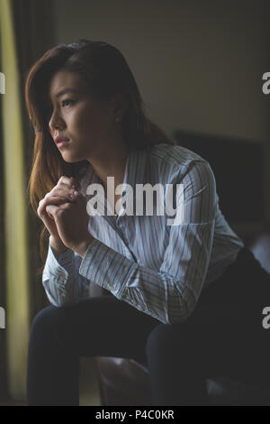 Thoughtful businesswoman sitting on armchair Banque D'Images