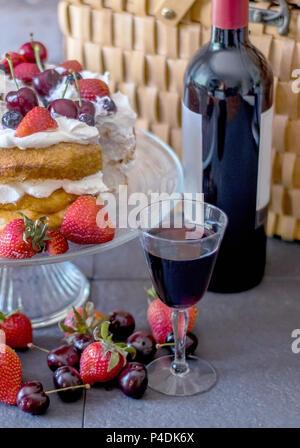 Vin rouge avec un frais angel food cake recouvert de baies. Un délicieux pique-nique! Banque D'Images