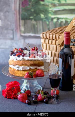 Pique-nique romantique avec un gâteau des anges fait maison recouvert de crème fouettée et de baies fraîches, et une bouteille de vin Banque D'Images