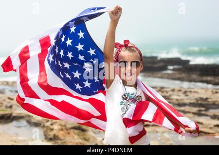 Drapeau américain est dans les mains d'une petite fille sur une plage de l'océan en Californie, États-Unis Banque D'Images