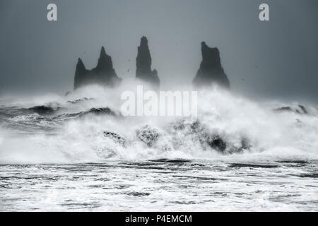 Vagues se briser contre les piles de la mer dans l'océan, l'Islande Banque D'Images