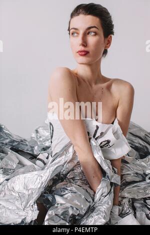 ... Femme portant une robe de papier assis sur feuille d argent Banque  D Images cc24dcc0fa56