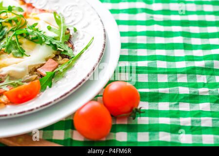 Oeufs au plat avec la roquette et les tomates cerise sur plaque blanche et tissu à carreaux. Copy space Banque D'Images