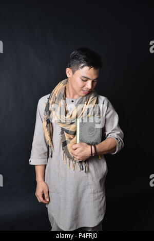 Musulman en vêtements traditionnels holding livre saint Coran Banque D'Images