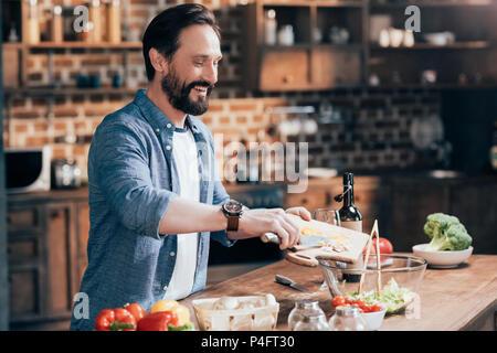 Homme barbu souriant salade de légumes de cuisson dans la cuisine Banque D'Images