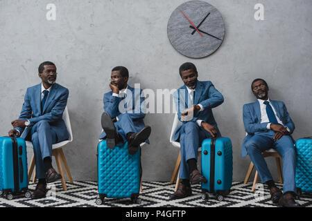 Les hommes d'affaires dans une salle d'attente avec des valises, même homme dans différentes poses Banque D'Images
