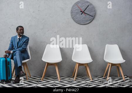 Handsome businessman dans une salle d'attente avec suitcase Banque D'Images
