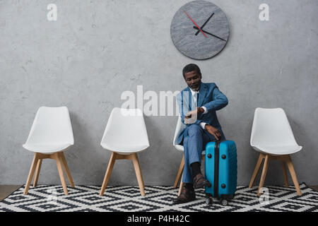 Handsome African American businessman dans une salle d'attente avec valise et looking at watch Banque D'Images