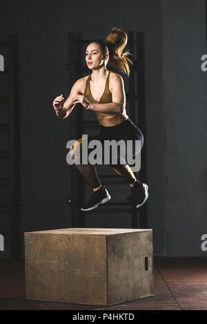 Les jeunes de la sportive de sauter sur un bloc en bois dans une salle de sport Banque D'Images