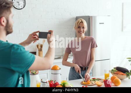 Vue partielle de l'homme prenant photo of smiling girlfriend la cuisson dans la cuisine à la maison, concept de vie végétalien Banque D'Images