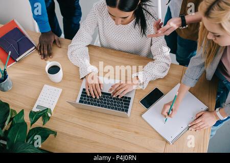 Vue supérieure de l'écriture d'affaires dans les études théoriques et de travail à table avec portable, smartphone, calculatrice et tasse à café Banque D'Images