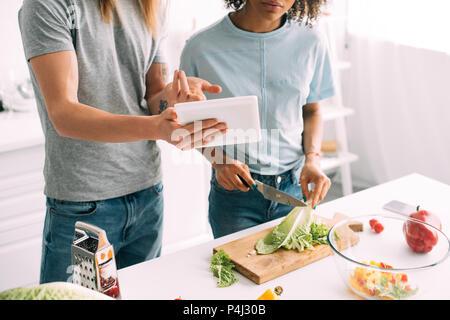 Cropped shot of homme pointant sur tablette numérique avec fiche de petite amie pendant qu'elle cuisine à cuisson Banque D'Images