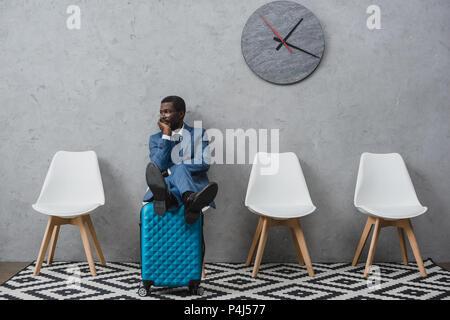 Handsome African American businessman dans une salle d'attente en mettant les jambes sur suitcase Banque D'Images