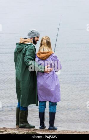 Jeune couple d'imperméables de pêche ensemble Banque D'Images