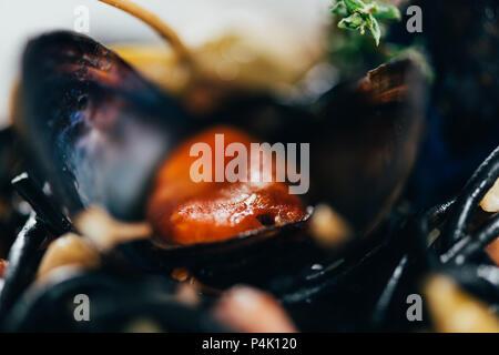 Spaghettis à l'encre de seiche gastronomique, les calmars et les moules avec Octopus Banque D'Images