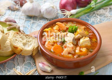 Soupe de poissons méditerranéens servis avec du pain blanc frais Banque D'Images