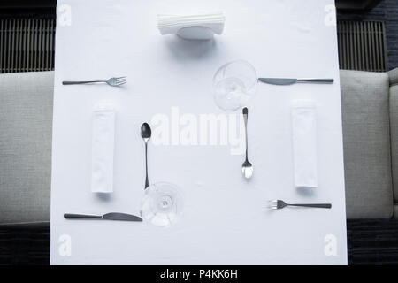 Vue de dessus de la coutellerie organisé et wineglasses sur table avec nappe blanche dans le