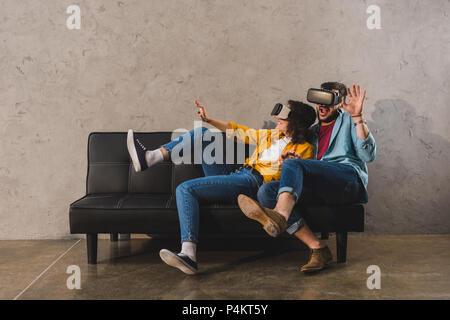 Peur jeune couple à l'aide de casque de réalité virtuelle sur la table Banque D'Images