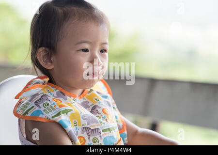 Close up Asain cute baby girl eatting eau glace sur chaise blanche. Banque D'Images