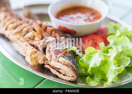 Gros poisson frais frit avec salade et sauce épicée, chaude style thai food concept. Banque D'Images