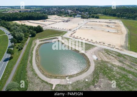 Vue aérienne d'un bassin d'eau de pluie et une nouvelle zone de développement dans le sable avec le planum de maisons nouvelles, prises à un angle, grande hauteur Banque D'Images