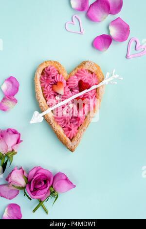 Tarte feuilletée en forme de coeur rempli de crème pâtissière rose pour la Saint-Valentin Banque D'Images