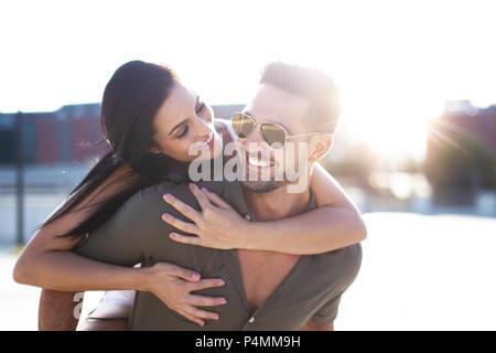 Happy young woman embracing man élégant de l'arrière à l'extérieur dans le coucher du soleil Banque D'Images
