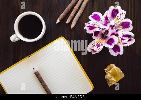 Bureau avec une machine à espresso Cup, ordinateur portable ouvert, Bouquet floral, crayons de couleur et de calcite Miel Banque D'Images