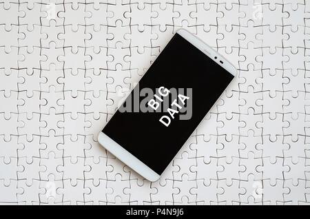 Un smartphone moderne avec un écran tactile se trouve sur un casse-tête blanche dans un état assemblé avec l'inscription. Le big data Banque D'Images