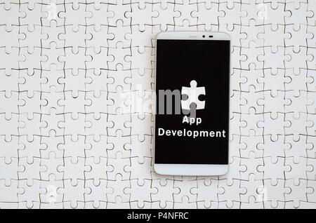 Un smartphone moderne avec un écran tactile se trouve sur un casse-tête blanche dans un état assemblé avec l'inscription. Le développement de l'app Banque D'Images