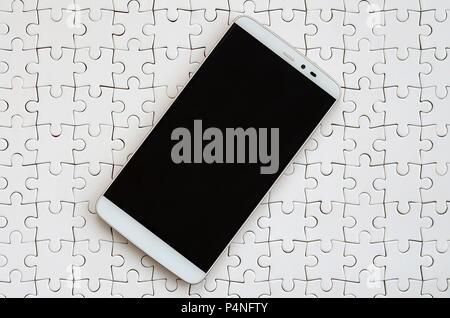 Un smartphone moderne avec un écran tactile se trouve sur un casse-tête blanche dans un état assemblé Banque D'Images
