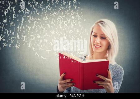 Belle fille blonde lire et battant lettres alphabet s'échapper du livre rouge. La magie des cours. Les jeunes enseignants de l'école, d'éducation et de l'étude Banque D'Images