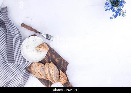 Yaourt au concombre. De dip frais taziki grec célèbre avec le concombre. pain frais, serviette et fond blanc. Copier l'espace. Banque D'Images