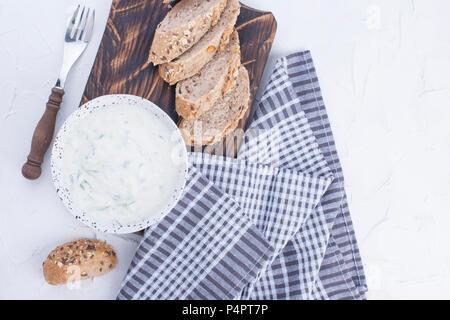 Yaourt au concombre. De dip frais taziki grec célèbre avec le concombre. pain frais, serviette et fond blanc. Copy space Banque D'Images