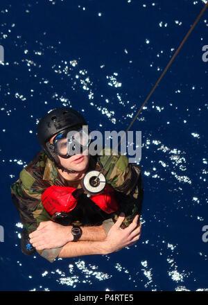 Le lieutenant de la Marine américaine j.g. David Carter, avec des explosifs et des munitions (unité mobile) EODMU 5, est hissé dans un hélicoptère HH-60H Seahawk affecté à l?compatible? De l'Escadron d'hélicoptères anti-sous-marin (HS) pendant 14 cast et le rétablissement de la formation dans l'océan Pacifique le 20 juillet 2010. EODMU-5 et HS-14 sont déployés à bord de l'avant-déployé porte-avions USS George Washington (CVN 73). (DoD Banque D'Images