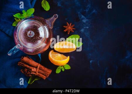 Petite théière en verre avec les tranches de citron, de cannelle et de feuilles de menthe sur un fond sombre. Des couleurs vibrantes boisson chaude still life with copy space. L'heure du thé télévision Banque D'Images