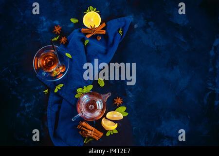 Le thé noir dans une tasse en verre et une petite théière avec les tranches de citron et feuilles de menthe sur un fond sombre. Les couleurs d'un plateau de coupe avec copie espace. Banque D'Images