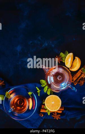 Tasse de thé et une petite théière avec les tranches de citron et feuilles de menthe sur un fond sombre. Des couleurs vibrantes boisson chaude still life with copy space. Location l'heure du thé Banque D'Images