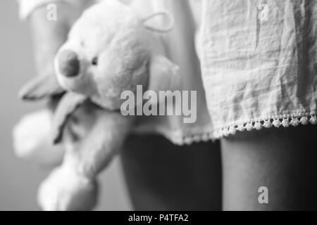 Ours en peluche dans une main de la jeune fille sur le fond de sa robe et la jambe Banque D'Images