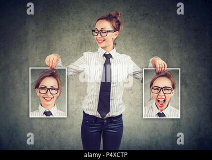 Jeune femme gaie dans les verres holding photos avec de bonnes et mauvaises émotions ayant de l'humeur et en souriant elle-même positive Banque D'Images