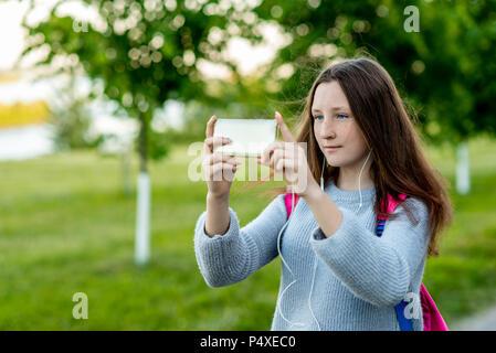 Belle fille écolière. À l'été dans le parc à la nature. Dans ses mains est titulaire d'un smartphone. Prendre des photos de paysage. Espace libre pour le texte. Elle sourit avec taches de rousseur sur son visage. Reste après l'école. Banque D'Images