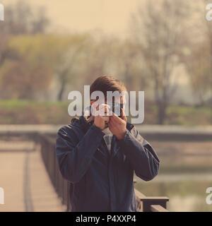 Photographies touristiques barbu avec enthousiasme la caméra. Photographier une vieille caméra sur l'emplacement. Banque D'Images