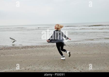 Pays-bas, happy blonde jeune femme s'exécutant sur la plage Banque D'Images