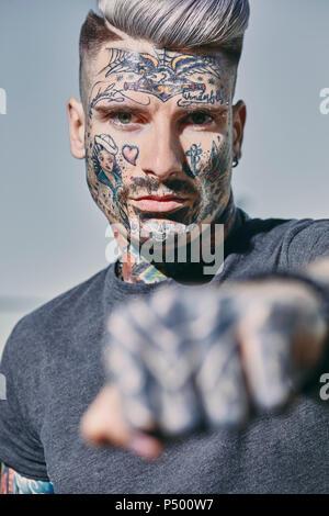 Portrait de jeune homme tatoué à l'extérieur de serrer son poing Banque D'Images